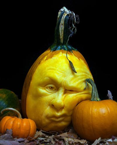 A pumpkin is leaning its face against a smaller pumpkin.